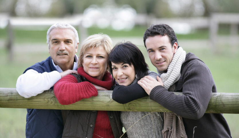 family-leaning-on-a-wooden-fence-post