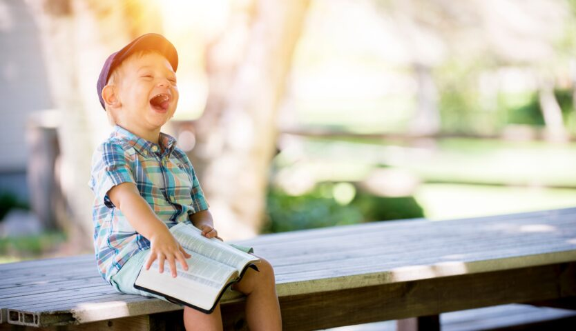 child-laughing-on-a-picnic-bench