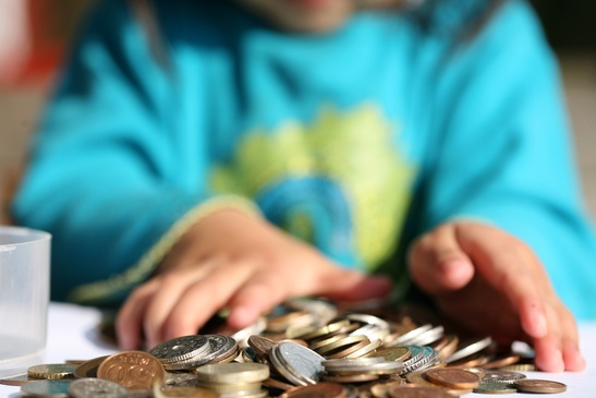 child's hands playing with a pile of coins