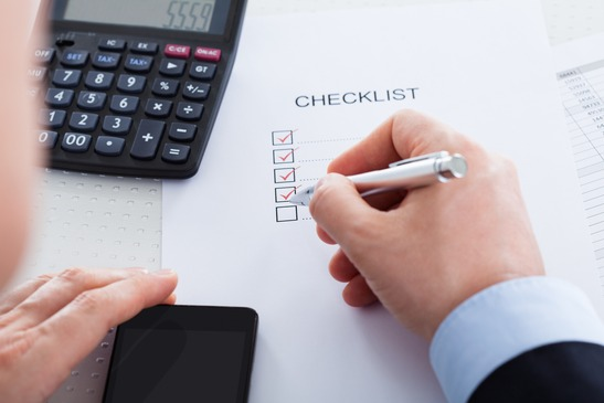 an-accountant-using-a-calculator-and-checklist