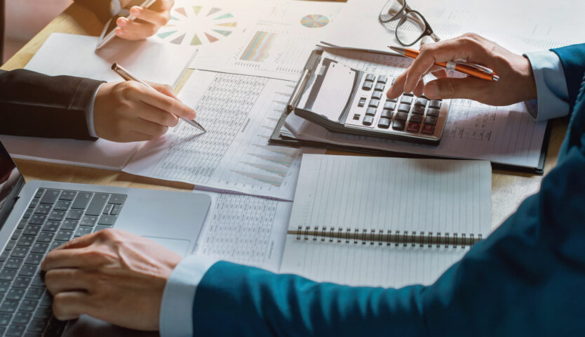 The hands of two accountants working on paper using a calculator