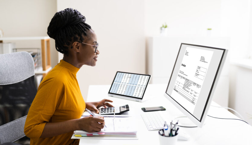 Accountant wearing a yellow shirt working on a computer