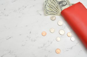 bills-and-coins-in-red-envelope-sitting-on-a-table