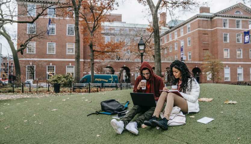 Two students sit on grass outside of a red brick university building