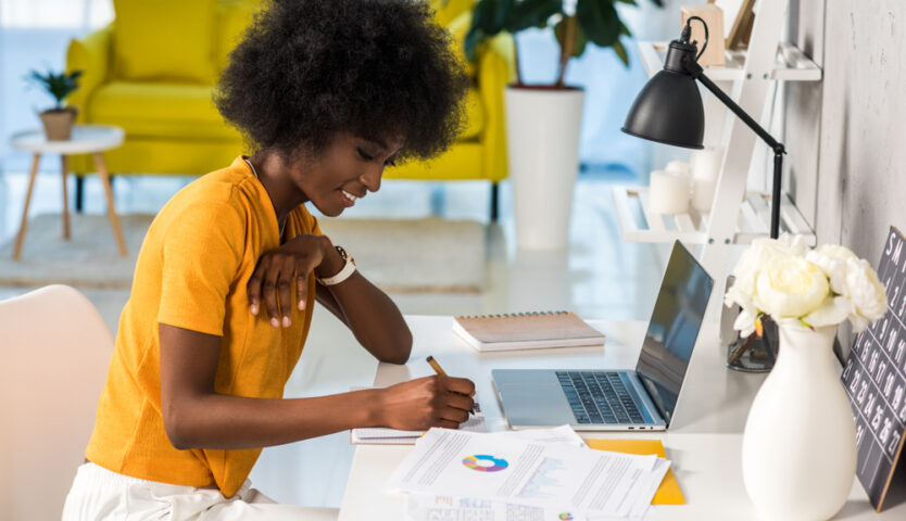 black woman in yellow shirt sitting at desk with laptop doing tax paperwork
