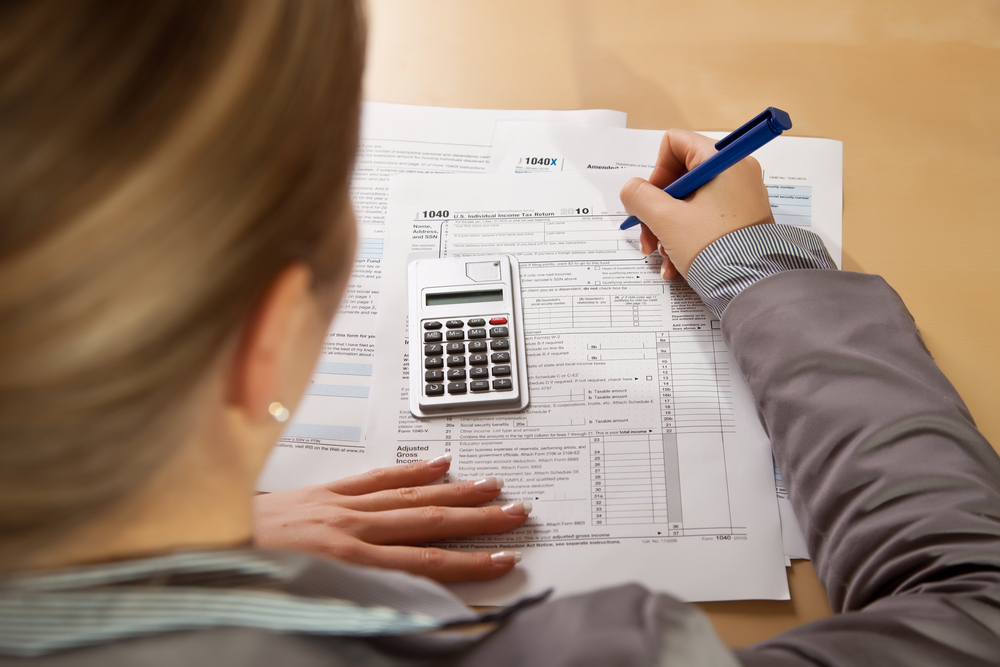 woman fills out tax form using pen and calculator