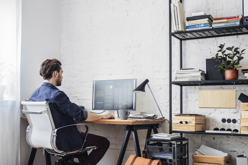 man sits in home office while working on computer
