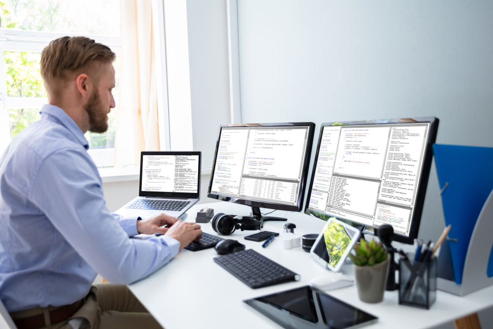 Computer programmer writing program code on computer in home office