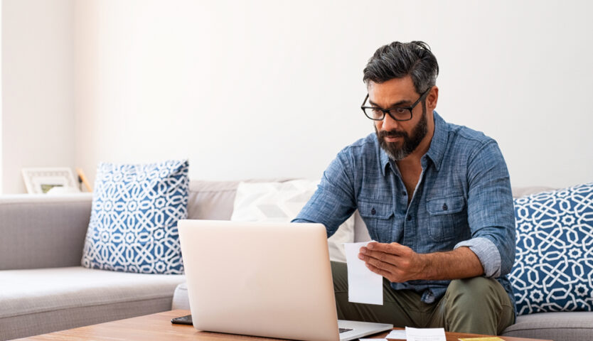 man with beard and glasses wearing denim shirt sitting a grey couch doing his taxes on his laptop
