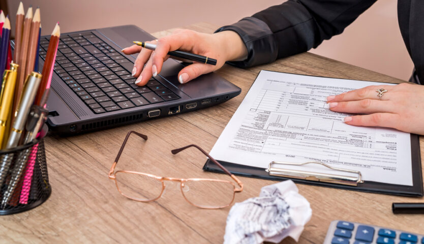 overhead photo of hands working on a laptop with eye glasses on desk and pencil holder on desk. crumbled paper is nearby.