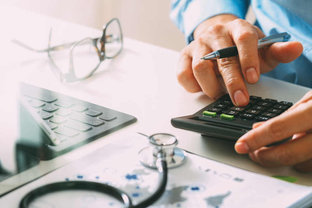 Man uses calculator on desk with stethoscope