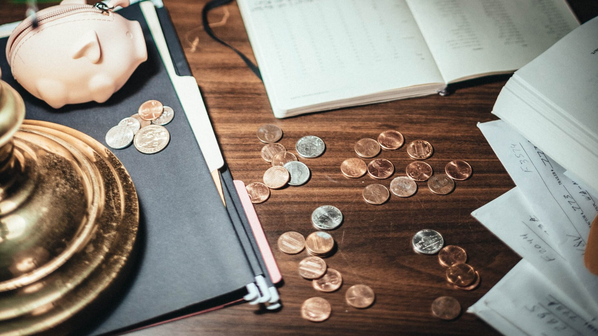 Wood desk with coins, piggy bank and accounting documents