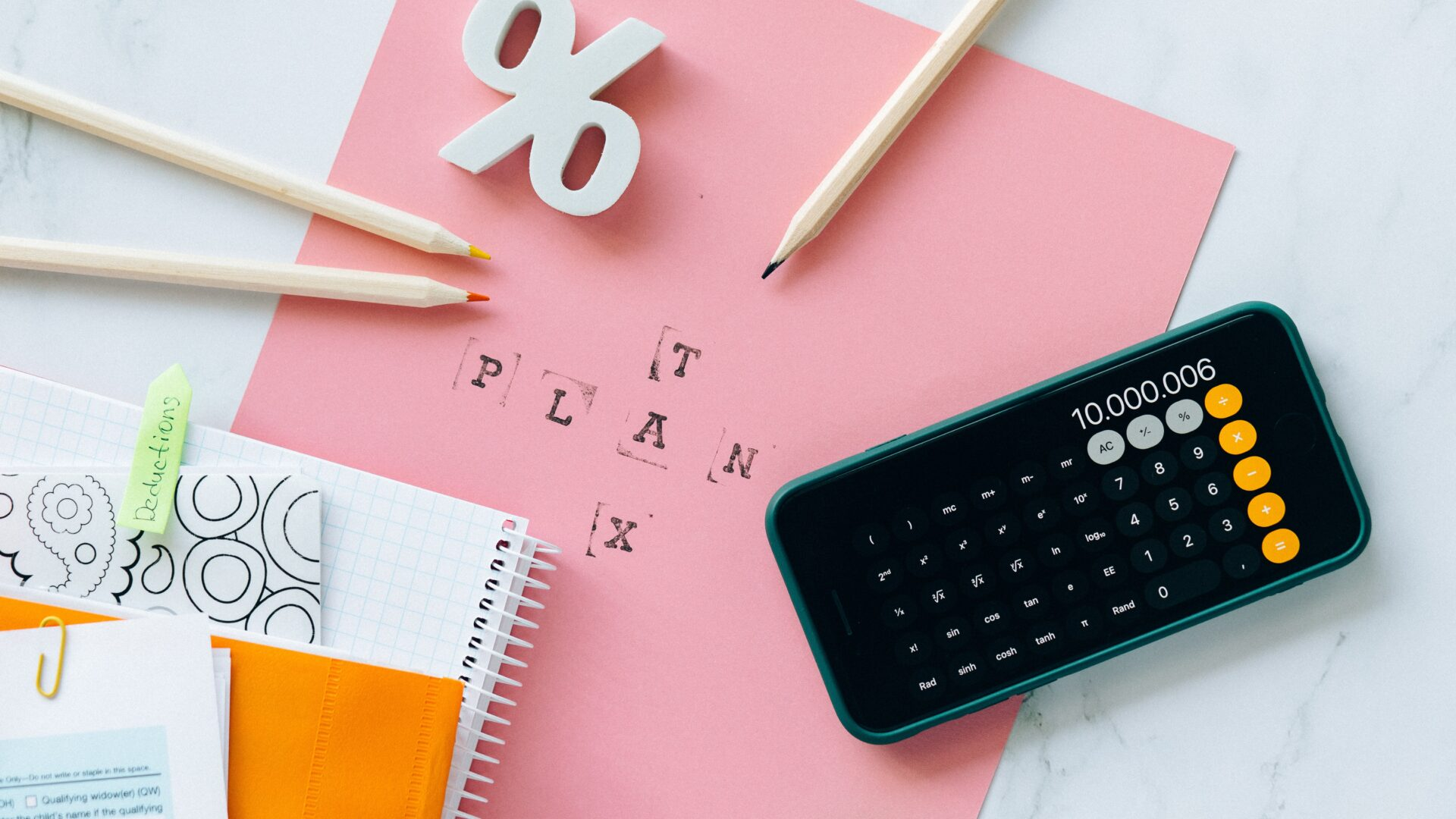 """Calculator on top of pink paper that reads """"tax plan"""""""