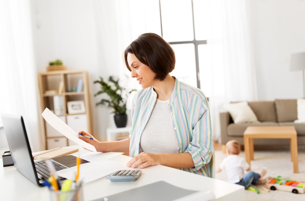 woman sitting at desk looking at paper and using calculator
